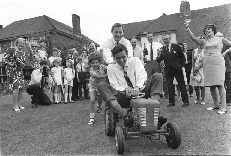 1966: Bette Hill throws her husband, motor racing ace Graham a party to celebrate his homecoming from America where he won the Indianapolis 500 in a Ford-Lola. Graham and his son Damon Hill push reigning World Formula 1 Champion Jim Clark around on a toy tractor. Mandatory Credit: Allsport Hulton/Archive