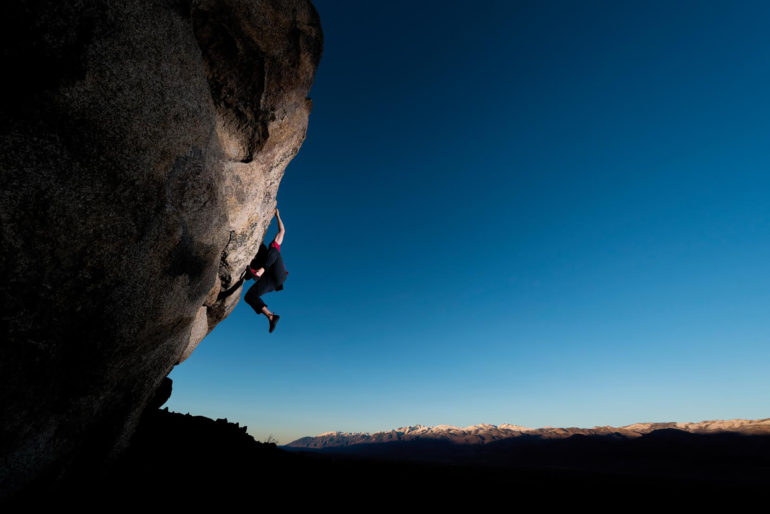 strong rock climber on a steep boulder during sunset, Location, Bishop CA USA