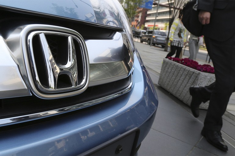 A man walks past a Honda on display at Honda Motor Co. headquarters in Tokyo. The Obama administration on Thursday, said it will fine Honda $70 million -- the largest civil penalty leveled against an automaker --- for not reporting to regulators over 1,700 complaints that its vehicles caused deaths and injuries and not reporting warranty claims