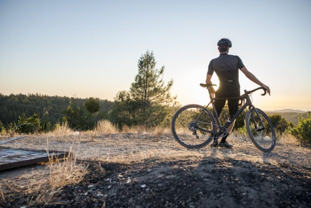 Bicicletta Ibis Hakka MX e biker che guardano il tramonto