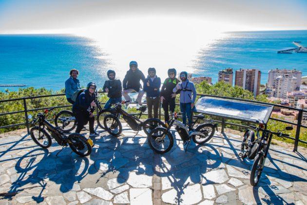 bicicletta elettrica bultaco albero, foto di gruppo con persone e mezzi sullo sfondo di Malaga