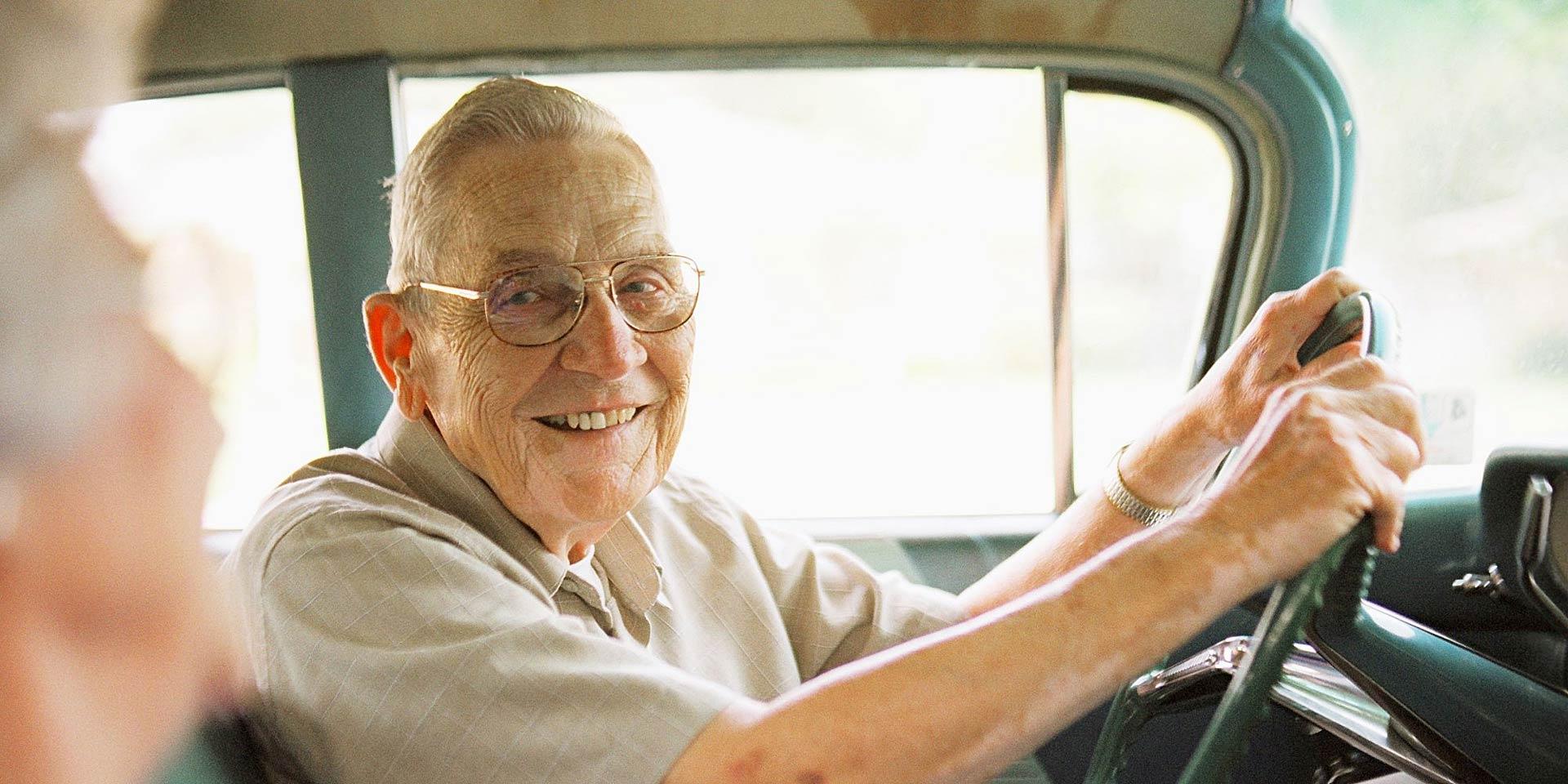 Anziano signore sorride alla moglie alla guida della sua auto