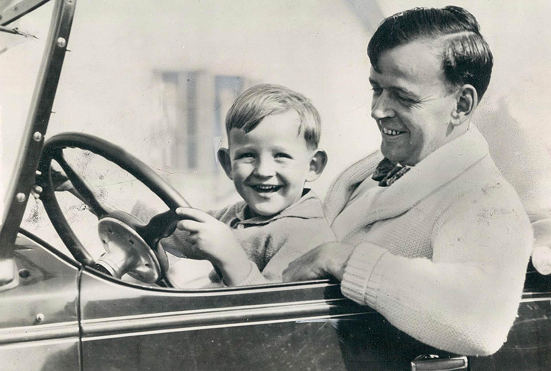 Il papà fa provare al figlio piccolo a guidare l'auto in bianco e nero