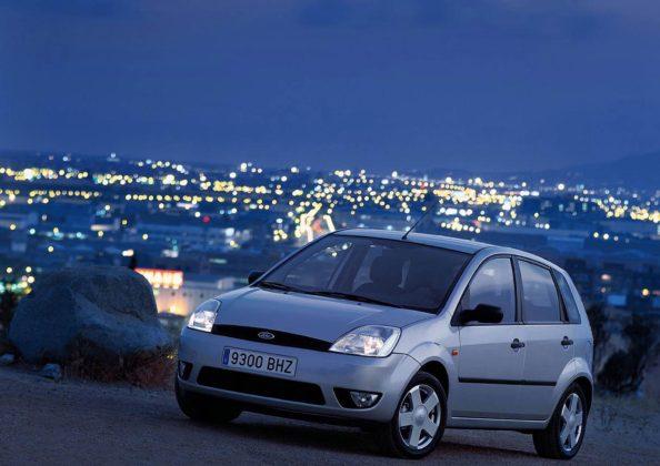 Ford Fiesta MKV grigia con sfondo di luci