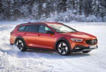 Opel Insignia Country Tourer 2018 arancione laterale in movimento sulla neve derapata