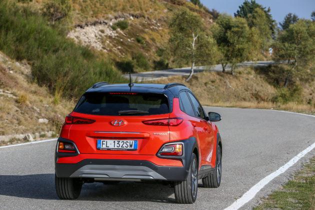 Hyundai Kona 2018 rossa 3/4 laterale posteriore destra in movimento su strada