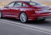 Nuova Audi A6 rossa 3/4 laterale posteriore sinistra in movimento su strada