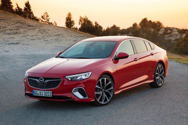 Opel Insignia GSi rossa 3/4 laterale anteriore sinistra statica su strada al tramonto