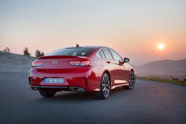 Opel Insignia GSi rossa 3/4 laterale posteriore destra statica su strada al tramonto