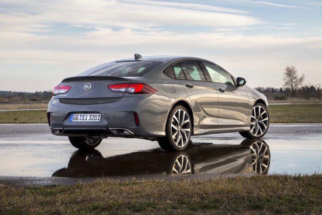 Opel Insignia GSi grigia 3/4 laterale posteriore destra statica su strada bagnata