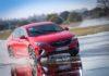 Opel Insignia GSi rossa 3/4 laterale anteriore destra in curva in movimento sul bagnato derapata