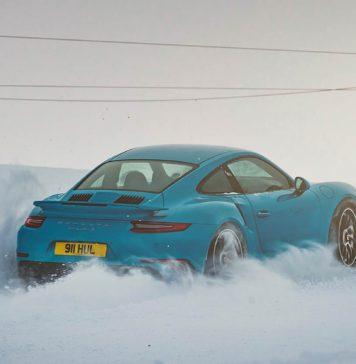 Porsche 911 azzurra immersa nella neve risale un pendio sollevando la neve