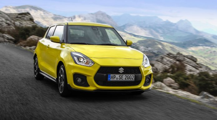 Suzuki Swift Sport 2018 3/4 laterale anteriore destro in movimento su strada gialla in montagna