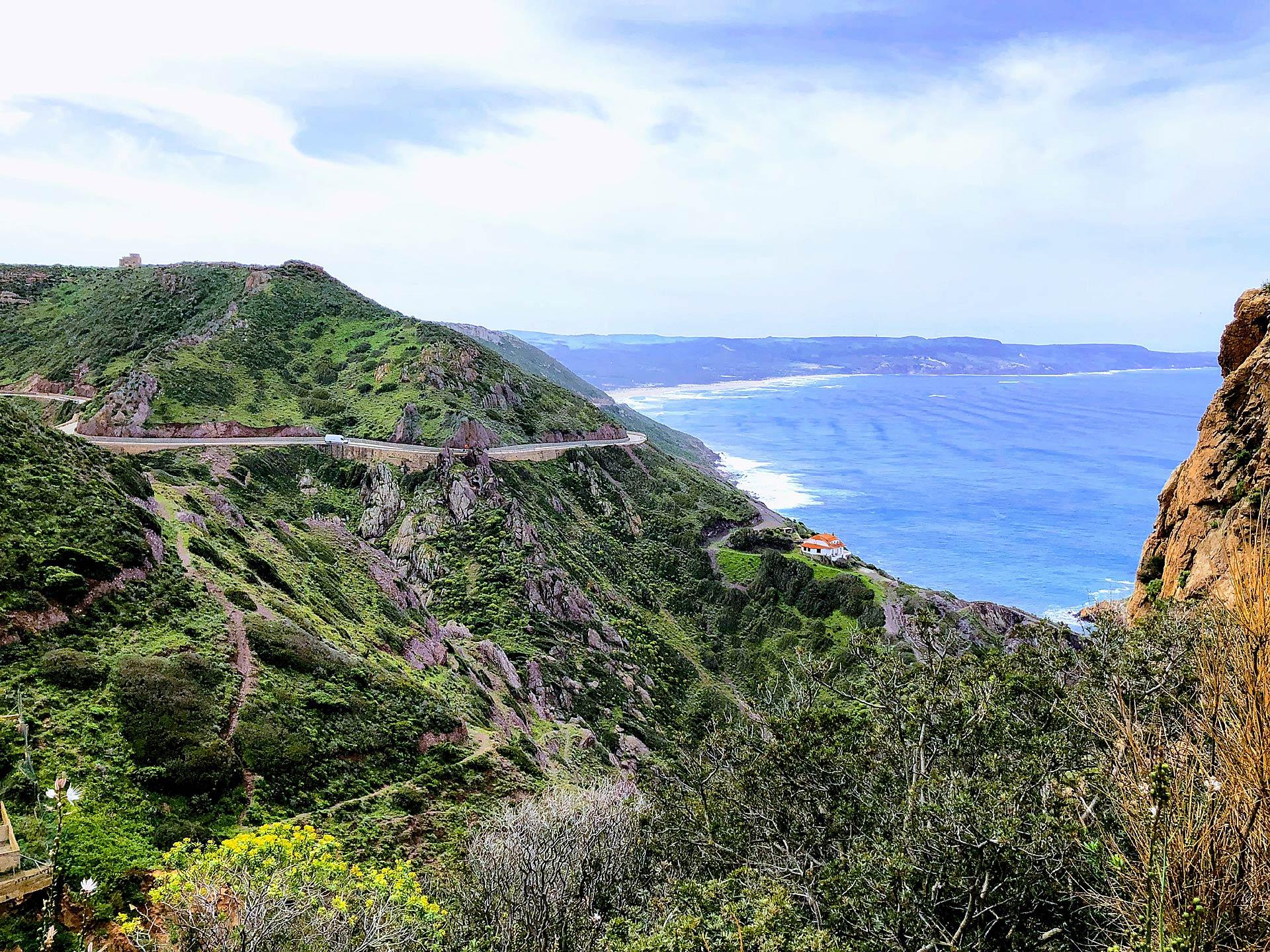 Vista dall'alto di una strada tortuosa della Sardegna del Sud, sullo sfondo si scorge il mare