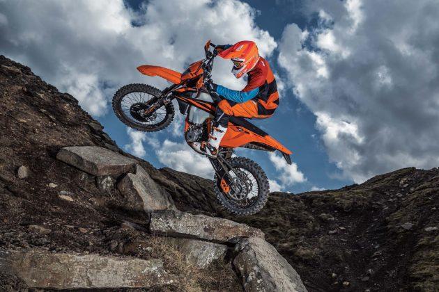 KTM EXC 2019 con pilota in movimento laterale su roccia