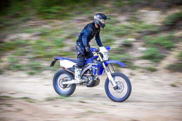 Yamaha WR250F laterale con pilota in piedi in movimento