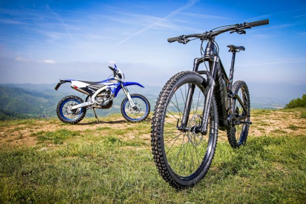 Canyon Spectral:ON 3/4 anteriore sinistra e Yamaha WR250F laterale destra