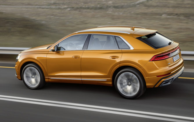 Audi Q8 laterale dragon orange su strada in movimento