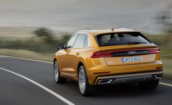 Audi Q8 dragon orange 3/4 laterale posteriore sinistra in movimento su strada
