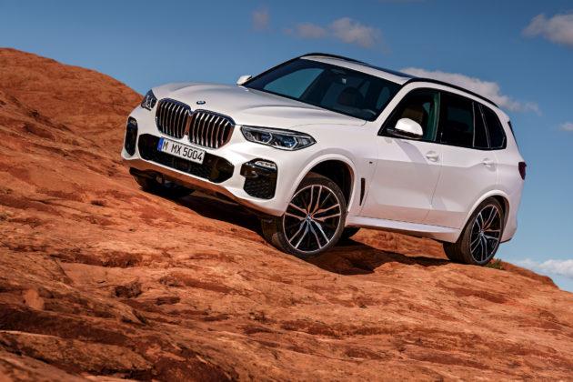 Nuova BMW X5 3/4 laterale anteriore sinistra in movimento su montagna bianca