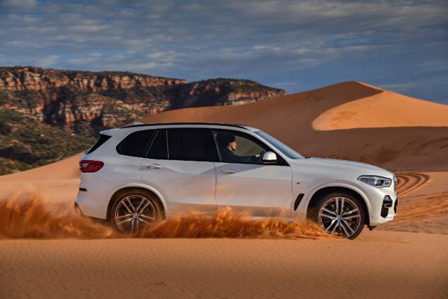 Nuova BMW X5 laterale destra bianca in movimento su sabbia