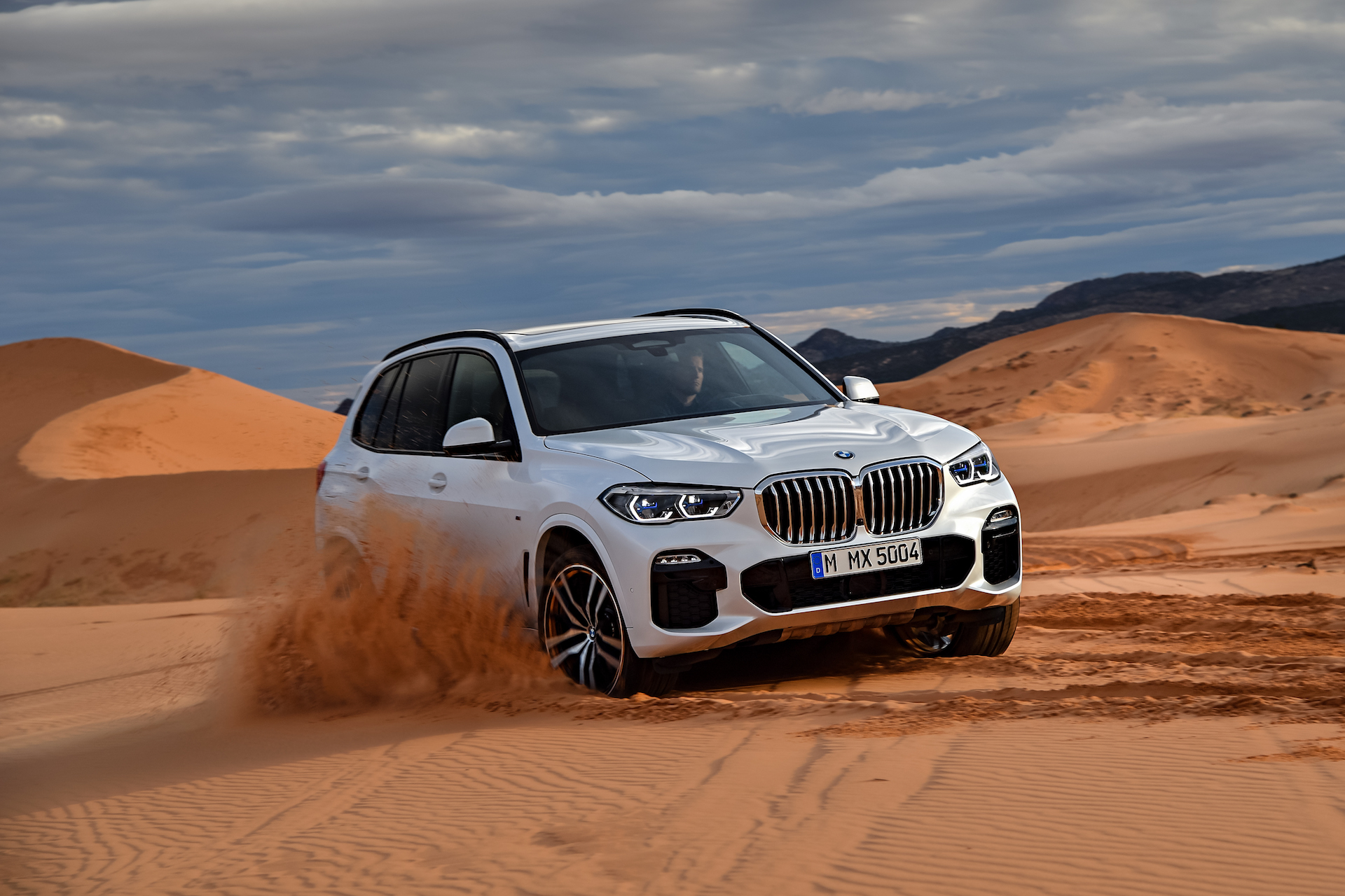 Nuova BMW X5 frontale in movimento su sabbia bianca
